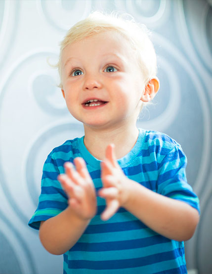Cute little toddler boy wearing a blue stripe shirt clapping hands at a Preschool & Daycare Serving Noblesville, IN