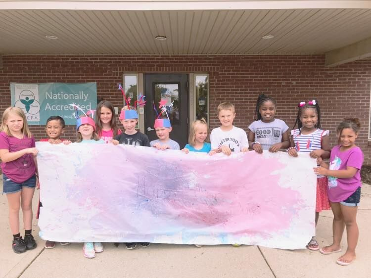 Preschool children holding a white with painted colors of banner at a Preschool & Daycare Serving Noblesville, IN