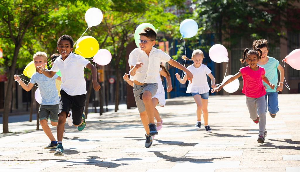 Group of happy kids with balloons running in race in the street and laughing outdoors at a Preschool & Daycare Serving Noblesville, IN