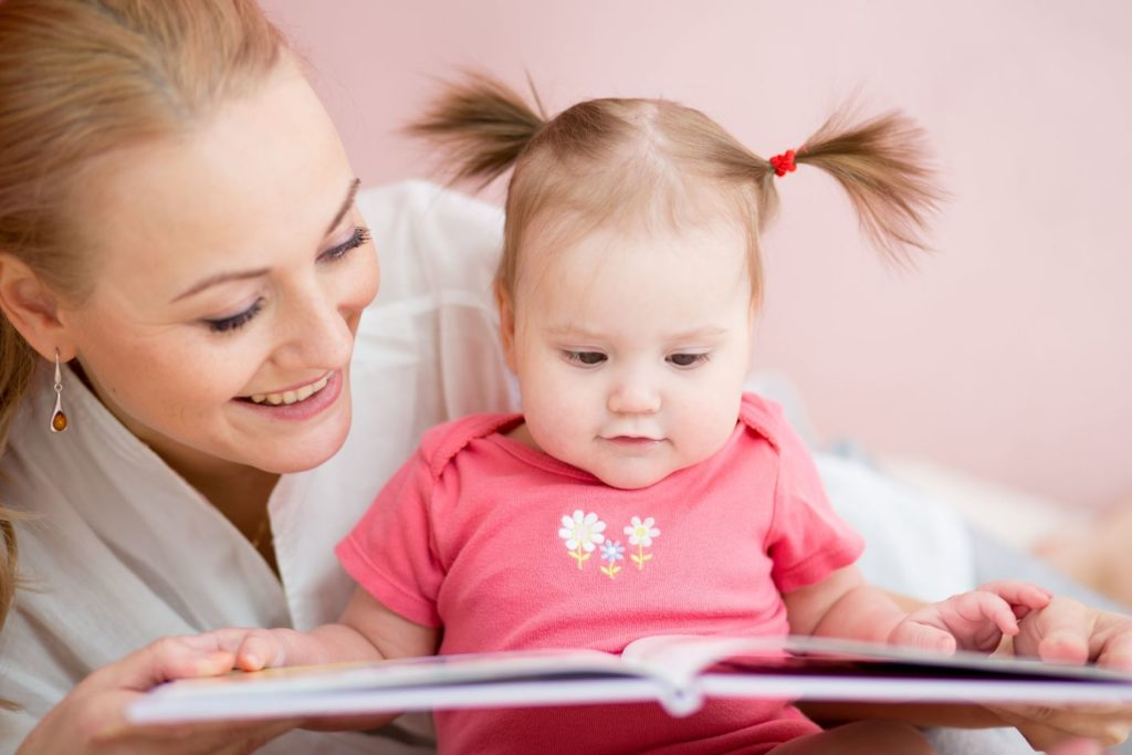 Mother reading a book to little baby girl at a Preschool & Daycare Serving Noblesville, IN