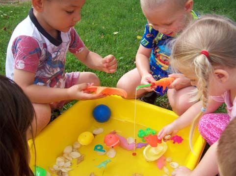 Group of young little preschool kids playing with water on a plastic container with toys in the garden at a Preschool & Daycare Serving Noblesville, IN