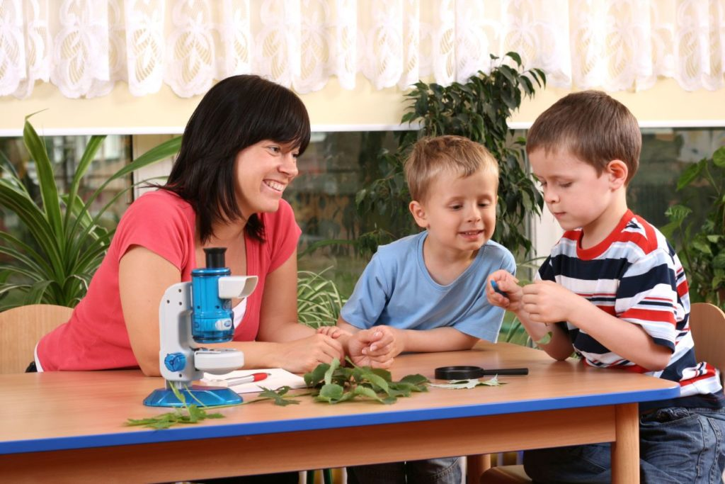 Preschool boys with teacher playing with some leaves and a toy microscope on wooden table at a Preschool & Daycare Serving Noblesville, IN