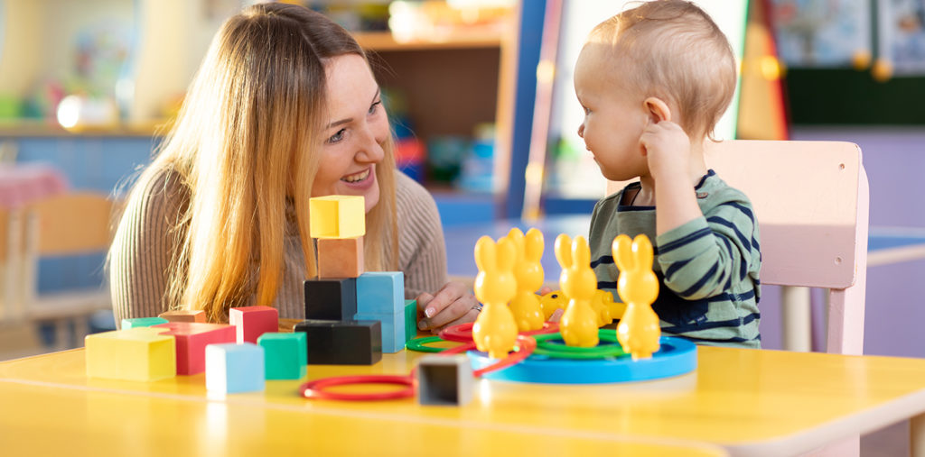 Kid and kindergarten teacher play with colorful wooden block toys on table at a Preschool & Daycare Serving Noblesville, IN