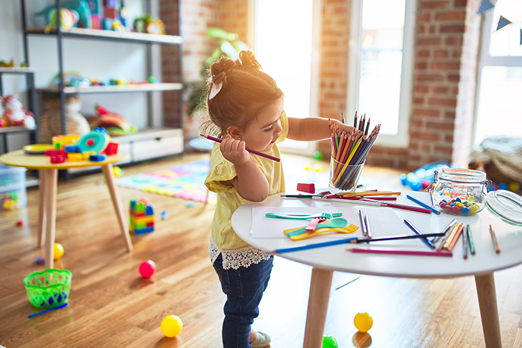 Beautiful toddler standing holding colored pencils at kindergarten at a Preschool & Daycare Serving Noblesville, IN