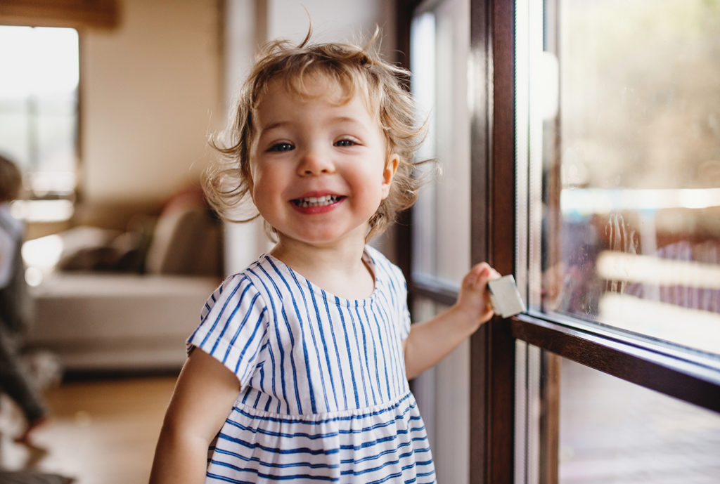 A happy toddler girl standing by window indoors looking at camera at a Preschool & Daycare Serving Noblesville, IN