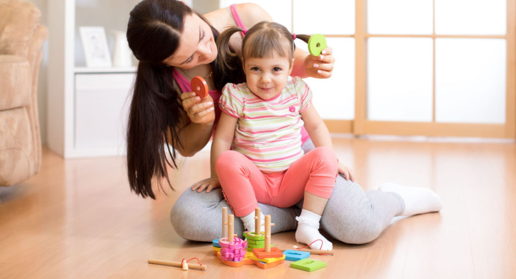 Mother and cute little daughter on ponytail sitting on ground playing with educational building blocks at a Preschool & Daycare Serving Noblesville, IN