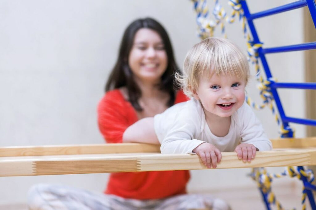 Teacher with a young little toddler boy enjoy climbing on the wooden bars at a Preschool & Daycare Serving Noblesville, IN