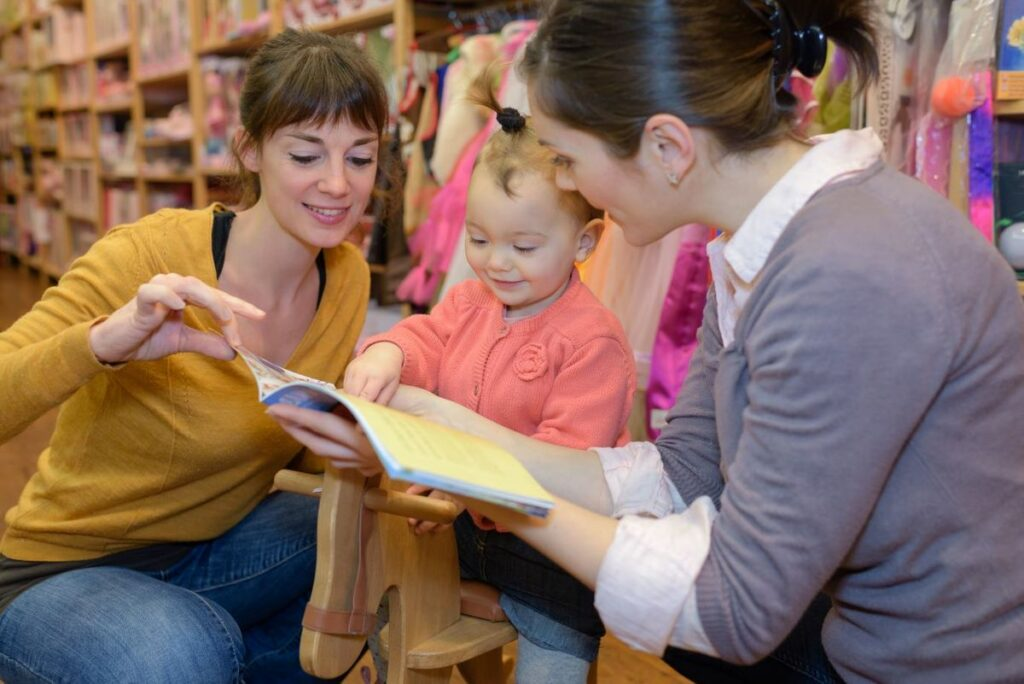 Teachers with a cute little toddler gild in ponytail reading a story book at a Preschool & Daycare Serving Noblesville, IN